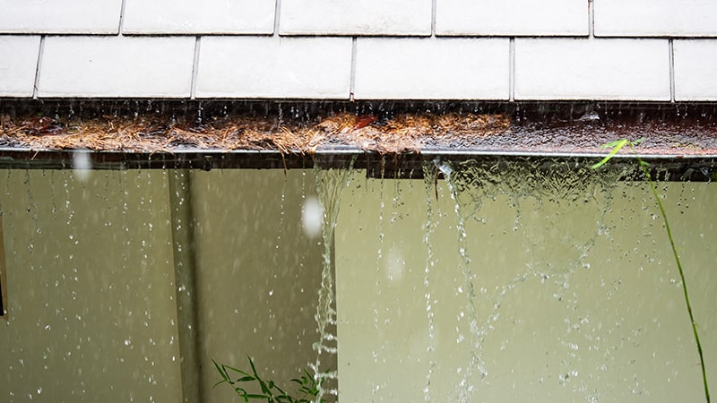 Water overflowing from gutters causing water damage to a home